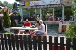 Två bord med fasta bänkar och en sittgrupp med ett litet bord och fyra små stolar: Svartådalens Café, Västerfärnebo.
